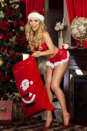Beautiful happy woman posing in Santa Claus costume. Christmas time.