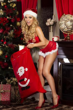 fille sexy: Belle femme heureuse posant � Santa Claus costume. La p�riode de No�l.