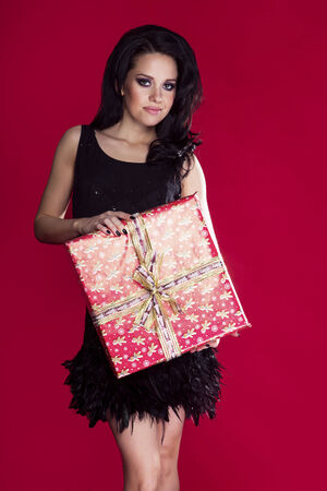 Elegant beautiful woman posing with gift over red background. Girl looking at camera, smiling. photo
