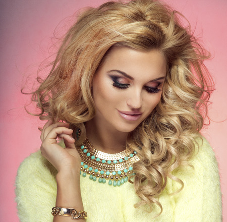Portrait of beautiful blonde woman with long curly hair and perfect makeup. photo