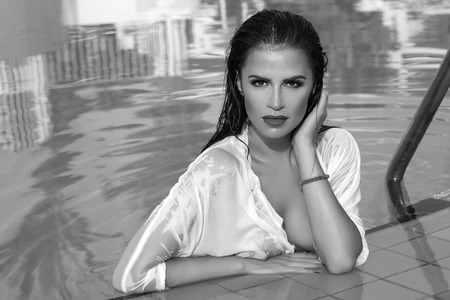 Beautiful brunette woman relaxing in swimming pool. photo