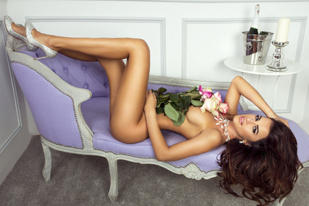 young girl nude: Naked brunette woman lying, posing with flowers. Stock Photo