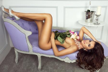 ragazza nuda: Nudo di donna bruna che giace, in posa con fiori.