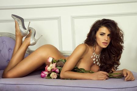 nudo integrale: Sensuale donna nuda in posa con fiori, guardando a porte chiuse. Archivio Fotografico