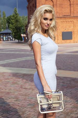 donna ricca: Bella bella donna bionda posa in vestito alla moda, guardando a porte chiuse.