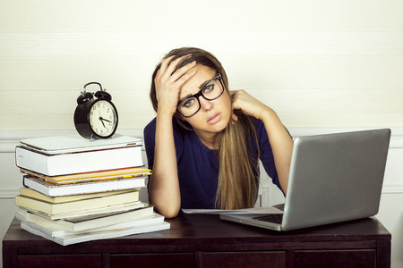 Young businesswoman sitting at desk and working. Sad beautiful woman.