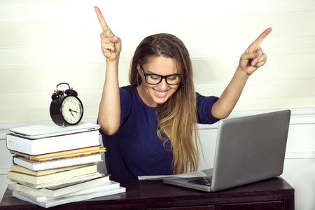 sitting at desk: Young businesswoman sitting at desk and working. Smiling .