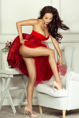 nudo integrale: Moda donna bruna che indossa elegante abito rosso, mostrando le gambe sottili.