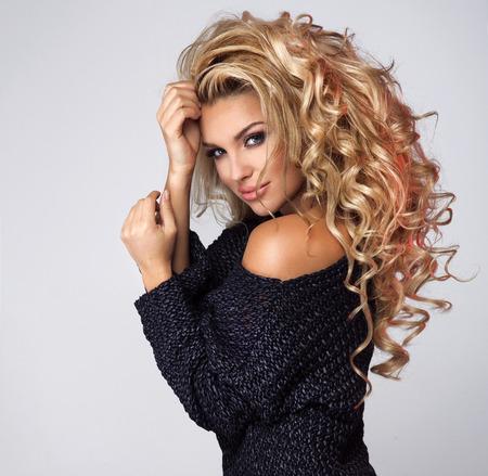 plan éloigné: Beauty portrait de femme blonde romantique avec de longs cheveux bouclés. Fille portant marine mode pull bleu. Studio, coup.