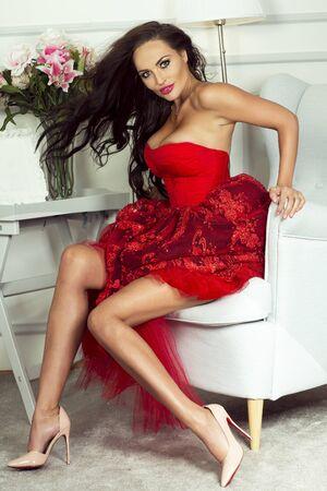 mujeres eroticas: mujer morena atractiva con las piernas largas y delgadas que presentan en la moda de vestir de color rojo. Hermosa chica con el pelo largo. Fotos en habitación elegante. tiro de interior.