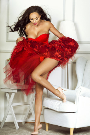 black breast: Sexy brunette woman with long slim legs posing in red fashionable dress. Beautiful girl with long hair. Photo in elegant room. Indoor shot.