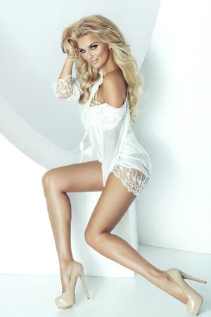 mujer sexy desnuda: Romántica joven rubia mirando a la cámara. Foto de moda. Chica con el pelo largo saludable y maquillaje perfecto. Estudio de disparo.