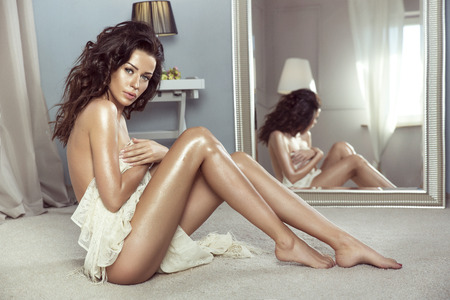 nudo integrale: Sensuale donna bruna posa nuda, seduta in bella camera, guardando a porte chiuse. La ragazza con la pelle lungo ricci hair.Perfect. Archivio Fotografico