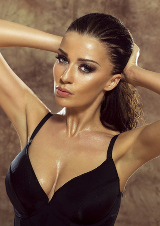 Sexy brunette woman posing with wet hair. Sensual lady. Studio shot.