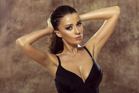 senos: Mujer morena sexy posando con el pelo mojado. Señora sensual. Estudio de disparo.