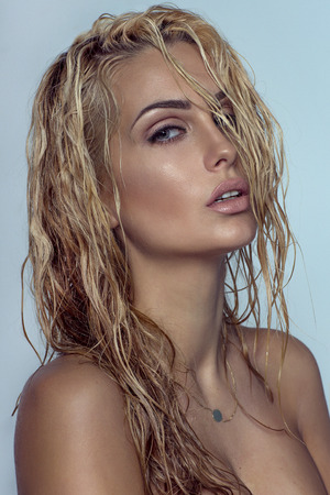 Closeup beauty portrait of blonde sensual woman with perfect makeup and wet hair. Stock Photo