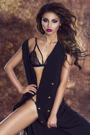 mujeres eroticas: Snesual dama morena posando en ropa interior de encaje, mirando a la cámara. Foto de archivo