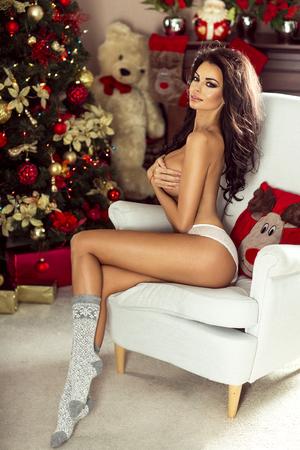 Schöne Brünette posieren über Weihnachten Hintergrund, in dem Kamera. Standard-Bild - 49214386