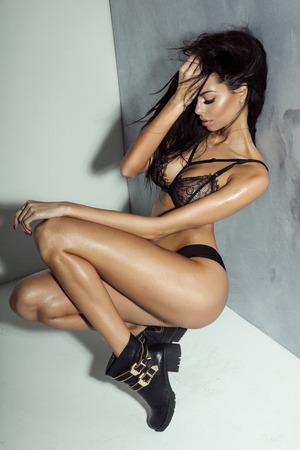 black girl nude: Sexy young brunette girl posing in black elegant lingerie. Perfect fit body. Studio shot.