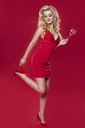 schwarze frau nackt: Schöne blonde Frau im roten eleganten Kleid aufwirft. Rotem Hintergrund. Lizenzfreie Bilder