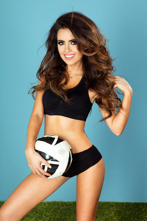 curvy woman: Sexy beautiful brunette young woman holding soccer ball, smiling, looking at camera.