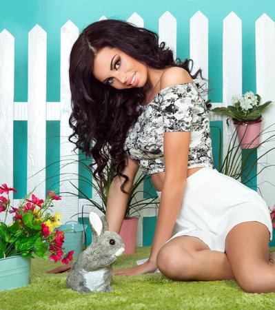 belle brune: jeune sexy belle femme avec de longs cheveux bouclés posant sur les fleurs. style de printemps. Fille brune.
