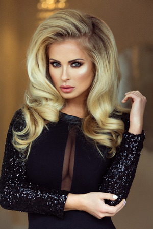 Portrait of sexy elegant blonde woman with long curly hair and glamour makeup. Stock Photo