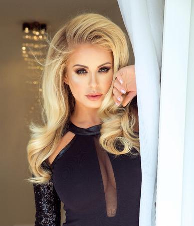 Retrato de la mujer rubia elegante atractivo con el pelo largo y rizado y maquillaje de glamour. Señora que mira a la cámara.