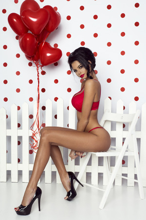 Beautiful sexy lady in red lingerie and slim tan body. Valentine's day.