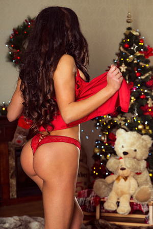 red lingerie: Sexy beautiful brunette woman in red lingerie. Christmas time.