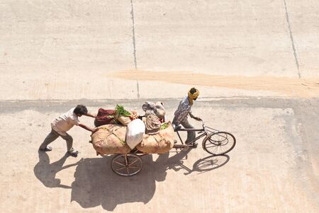 Indian rickshaw loaded with cargo, way to the bazaar