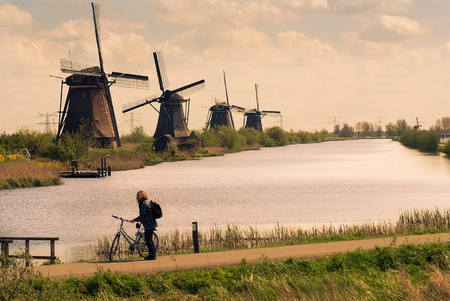 summer dutch landscape with windmills and tourist with bike photo