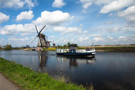 dutch landscape with windmills and tourist boat photo