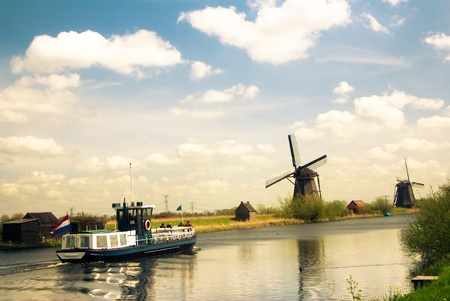 summer dutch landscape with windmills and tourist boat photo