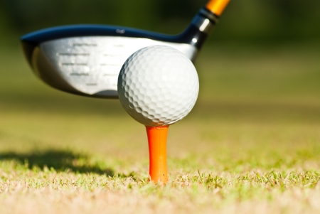 golf ball and driver behind photo