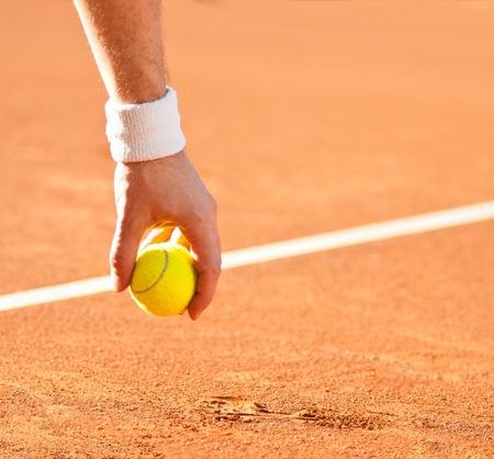 tennis stadium: pelota de tenis amarilla en la mano