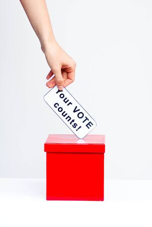 opinion poll: hand putting ballot into ballot box Stock Photo