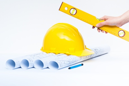 architect tools: architect holding yellow spirit level and construction tools