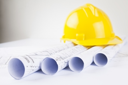 rolls of architectural projects and yellow hard hat Stock Photo