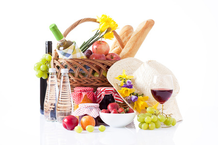 picnic basket with bottle of wine,fruits, bread and summer hat isolated on white