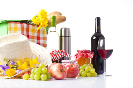 picnic basket with bottle of wine,fruits, bread and summer hat isolated on white photo