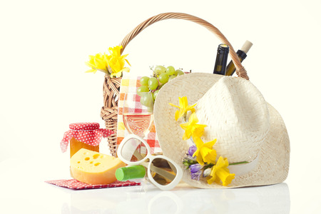 picnic basket with wine, fruits and summer hat isolated on white photo