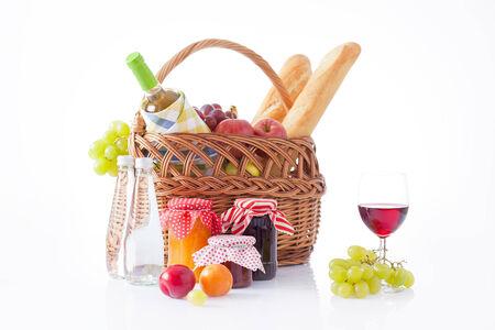 canasta de frutas: cesta de picnic con vino, pan, frutas y manta de picnic Foto de archivo