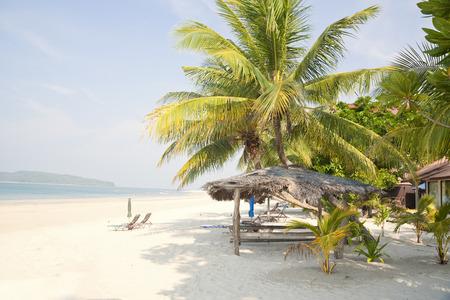 Lounges under an umbrella on sandy beach  photo