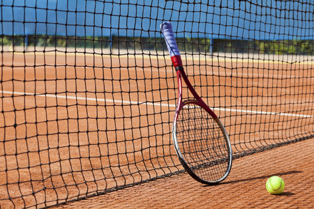 tennis racket and ball on clay tennis court