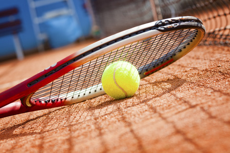 view of tennis racket and ball on the clay tennis court