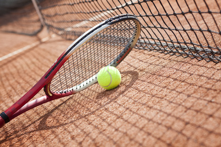 Close up view of tennis racket and ball on the clay tennis court Stock Photo