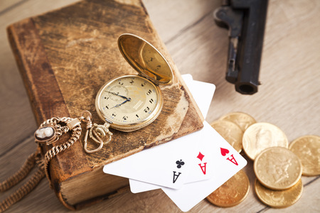 gambling and crime concept with gun, cards and golden coins photo