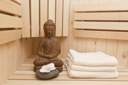 spirituality therapy: finnish sauna with buddha statue, relaxation and meditation concept
