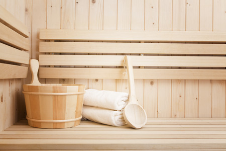 Detail of bucket and white towels in a sauna, wellness and relaxation background